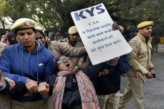 A protester against the Citizenship (Amendment) Act being detained outside a government office for the state of Assam, New Delhi, India, December 23, 2019