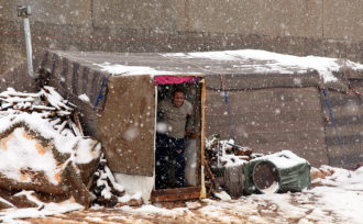 A Syrian refugee looking out of his makeshift tent dwelling in Amman, Jordan, December 12, 2013