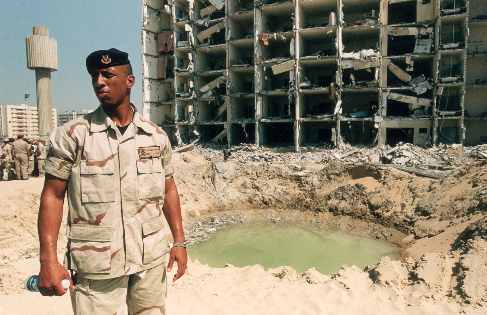 A US Air Force sergeant standing next to the terrorist bomb crater at Khobar Towers, 1996