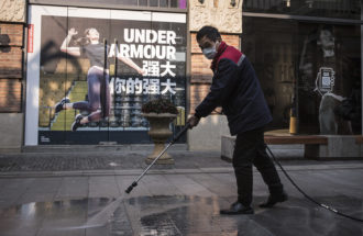 A street-cleaner working in a virtually deserted shopping precinct during the coronavirus lockdown of Wuhan, Hubei province, China, February 3, 2020
