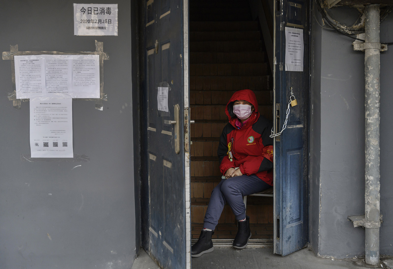 A neighborhood committee member guarding the entrance of a residential building as efforts continued to control the spread of coronavirus infection, Beijing, China, February 28, 2020