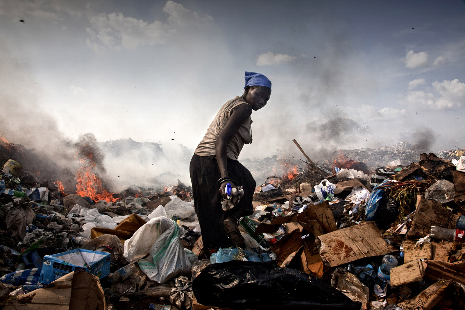 A woman walking through the landfill where she lives, Juba, South Sudan, 2010