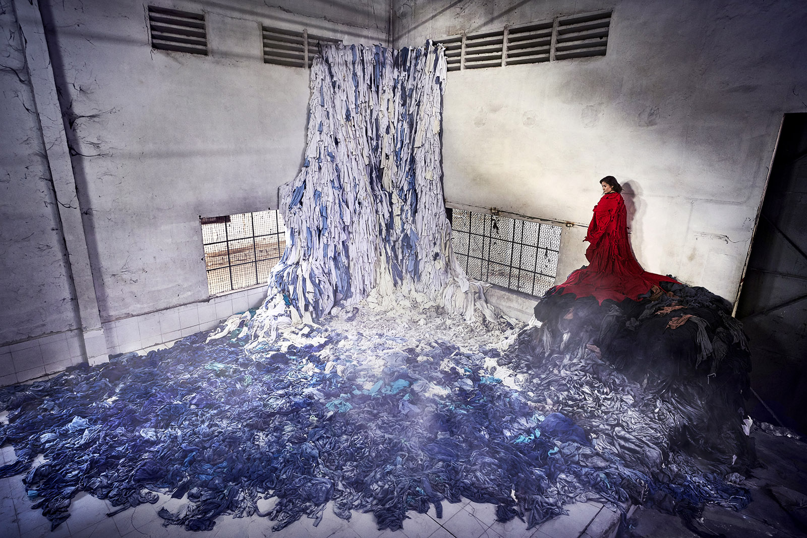 An installation made from clothes found in the abandoned Tak Fak garment factory in Cambodia, representing the more than seven hundred gallons of water required to grow the cotton for one T-shirt; from 'Clothing the Loop,' by Von Wong and Laura Francois, 2018