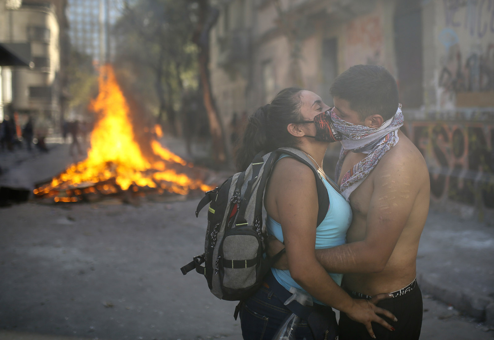 A couple kissing next to a burning barricade, Chile