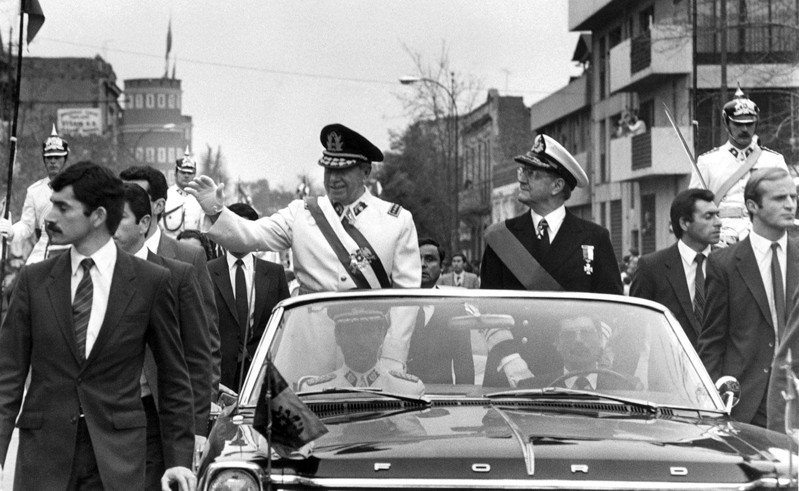 General Augusto Pinochet waving from a motorcade