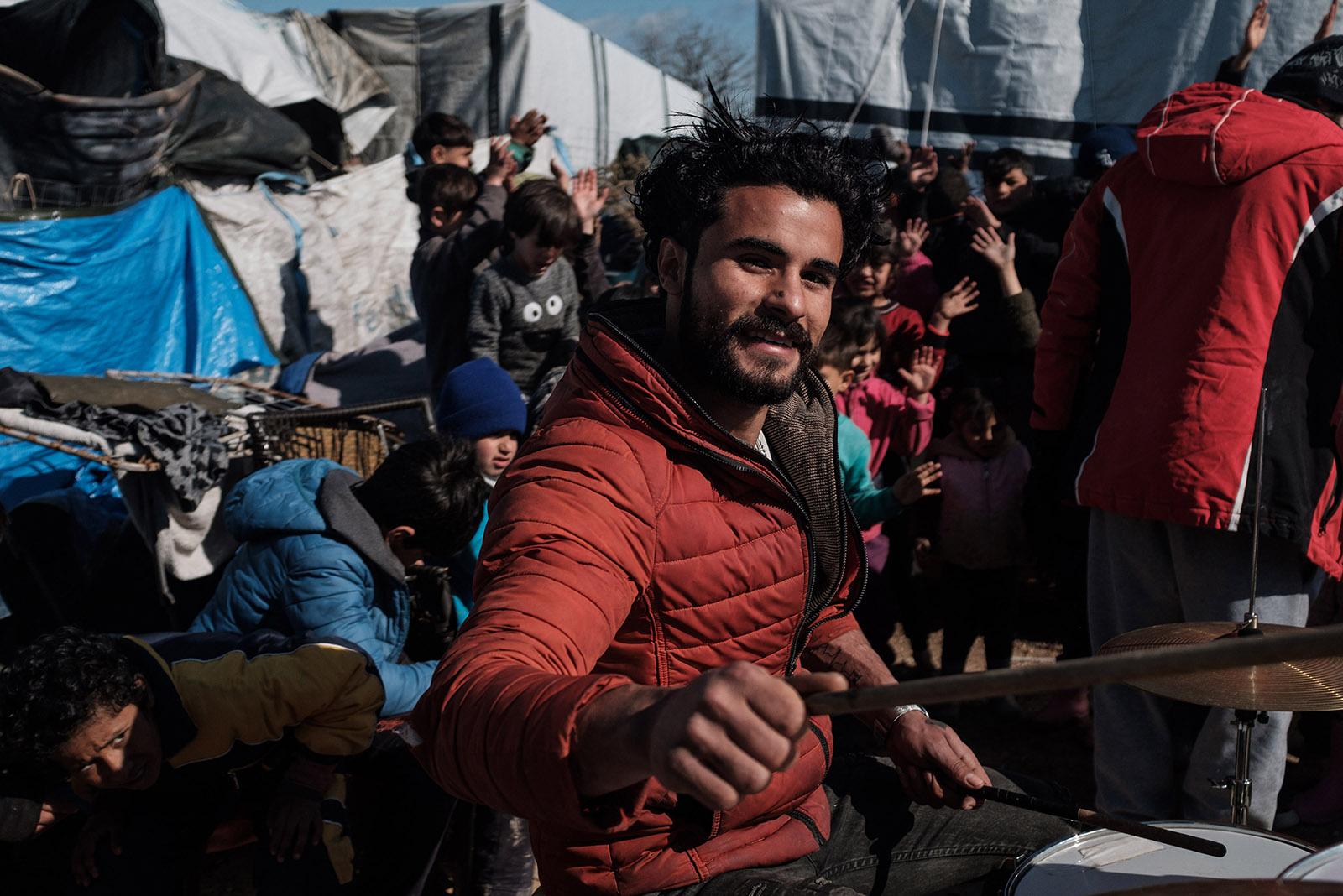 An asylum-seeker playing on a makeshift drum kit