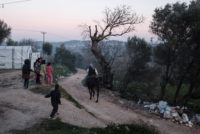 Refugee children watching a Greek villager riding by their camp, Chios, Greece, February 2020