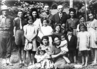 The elderly Aristide Gasnier, mayor of Vibraye, with two US soldiers and some of the Jewish refugees he helped save during the Nazi occupation; Huguette stands directly in front of Gasnier; her older brother Maurice is the boy at the far right. Sarthe, France, 1944