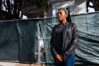 "Moms 4 Housing activist Dominique Walker standing in front of 2928 Magnolia Street, the house the group occupied starting in November 2019, declaring that housing is ""a human right,"