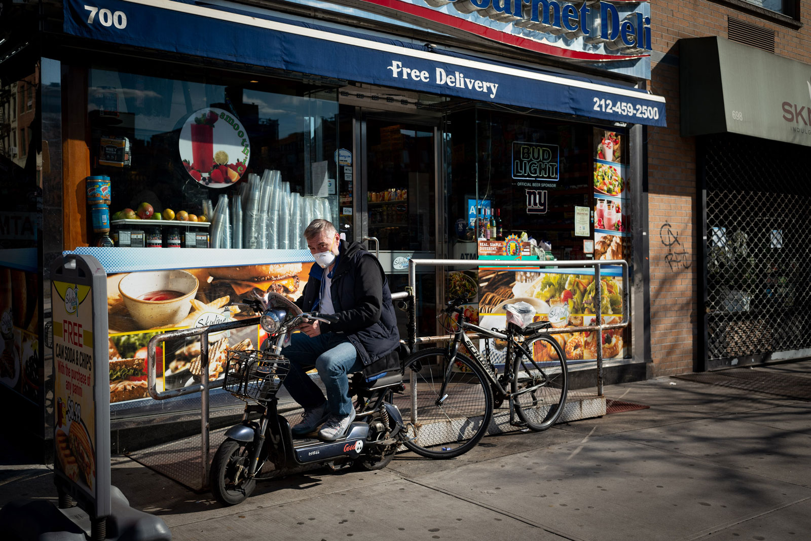 A man reading the paper outside a deli on Tenth Avenue, Hells Kitchen, New York City, March 24, 2020