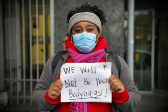"""A protester demanding safer working conditions and better protective equipment at a """"Covid-19 Frontline Health Worker Action"""" event, New York City, April 6, 2020"""