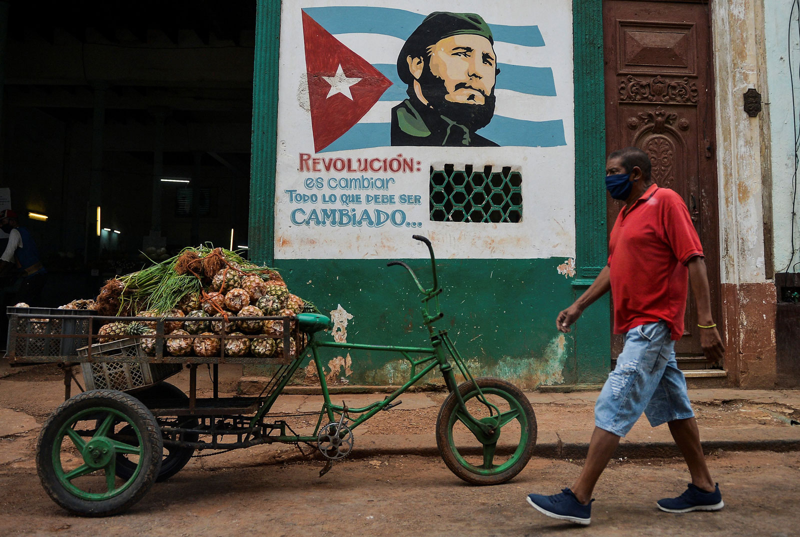 A man wearing a face mask walks by a mural depicting Fidel Castro in Havana, Cuba, May 13, 2020