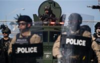 A police officer armed with a semi-automatic carbine watching from an armored vehicle during a rally protesting the death in police custody of George Floyd, Miami, Florida, May 31, 2020