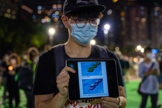 A participant displaying images on a tablet device at a vigil in Victoria Park linking pro-democracy protests with the 1989 Tiananmen Square in China, Hong Kong, June 4, 2020