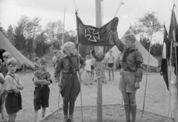 Youth members of a German-American Bund camp raising a flag at half-mast in tribute to Nazi Germany's late President Hindenberg, Griggstown, New Jersey, August 1934