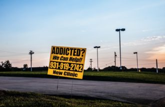 In the field where Dr. Samson Orusa's clinic used to stand, a sign directing patients to a local Suboxone clinic, Clarksville, Tennessee, July 15, 2020