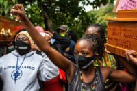 The widow of Cosmas Mutethia, who was killed by Kenyan police during a night curfew, helping to bear a symbolic coffin at a protest outside the Kenyan Parliament, Nairobi, Kenya, June 9, 2020