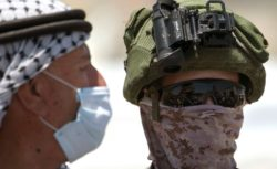 A Palestinian protester and an Israeli soldier during a rally against Israel's plan to annex parts of the occupied West Bank, Haris, near Nablus, West Bank, June 26, 2020