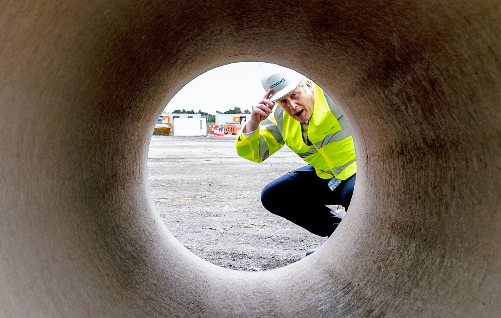 Prime Minister Boris Johnson looking through a pipe during a visit to a Siemens Rail factory construction site, Goole, England, July 6, 2020
