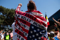 A woman draped in a flag with the names of Native American people who have been killed, at a demonstration outside the American Indian Center, Minneapolis, Minnesota, June 7, 2020