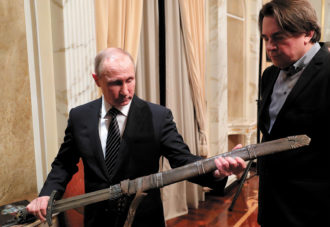 Vladimir Putin and Konstantin Ernst admiring a replica sword from a film produced by Ernst, Moscow, December 2016