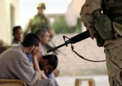 US Army soldiers guarding detainees during a raid on a house in Tikrit, Iraq, 28 July 2003