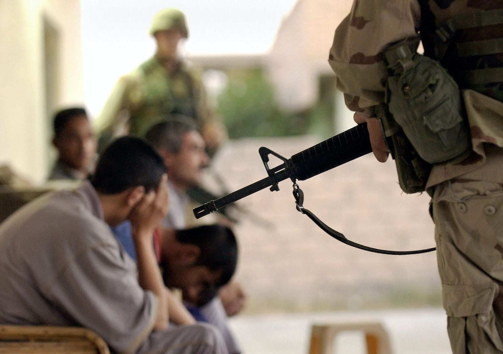 US Army soldiers guarding Iraqi detainees, 2003