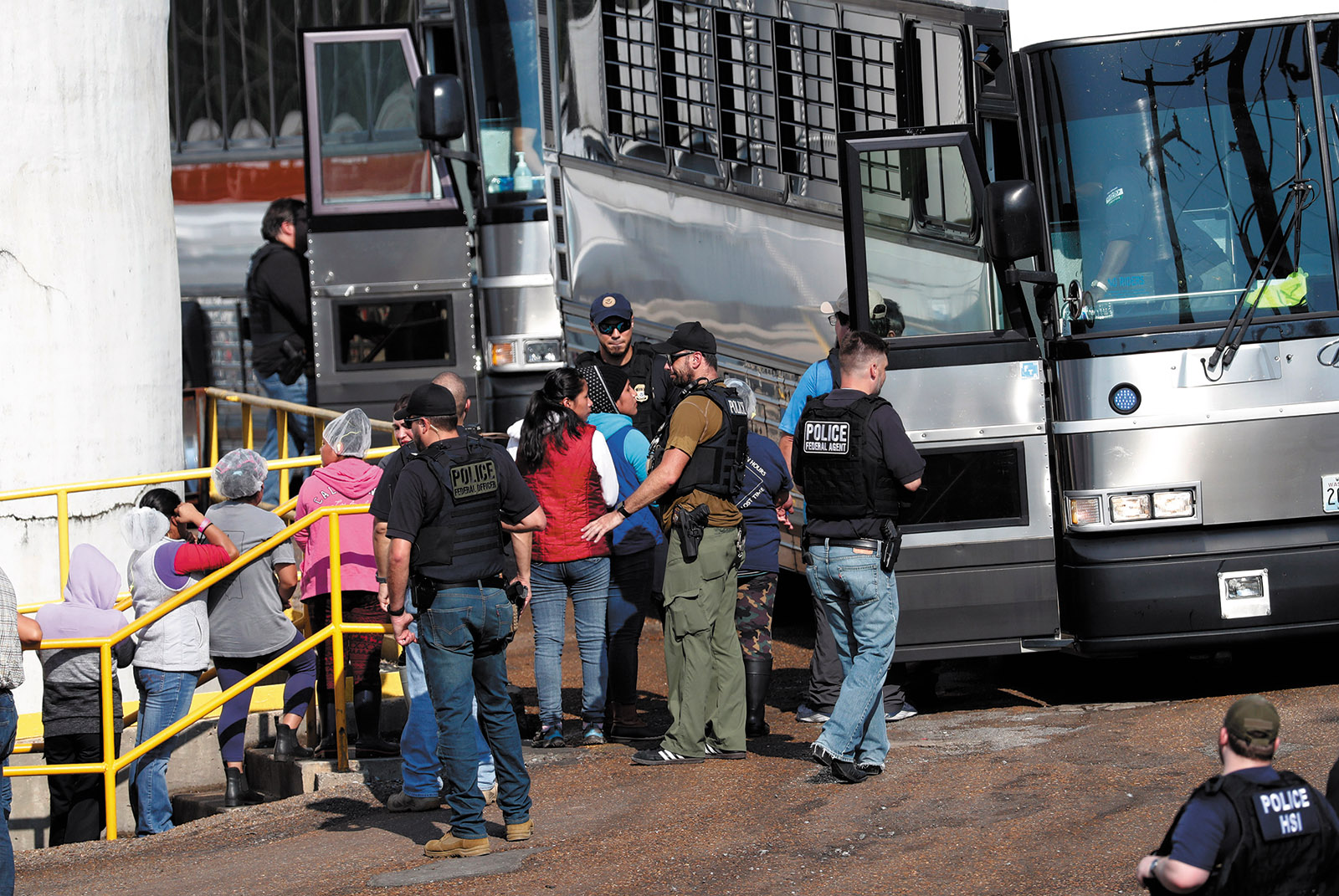 Workers from a Koch Foods plant being taken away by ICE agents during a raid, Morton, Mississippi