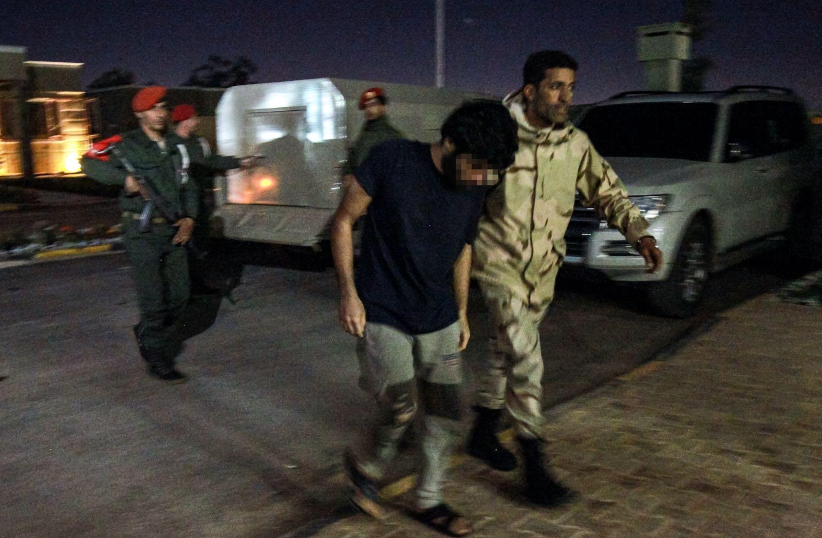 Prisoner escorted by Libyan soldier
