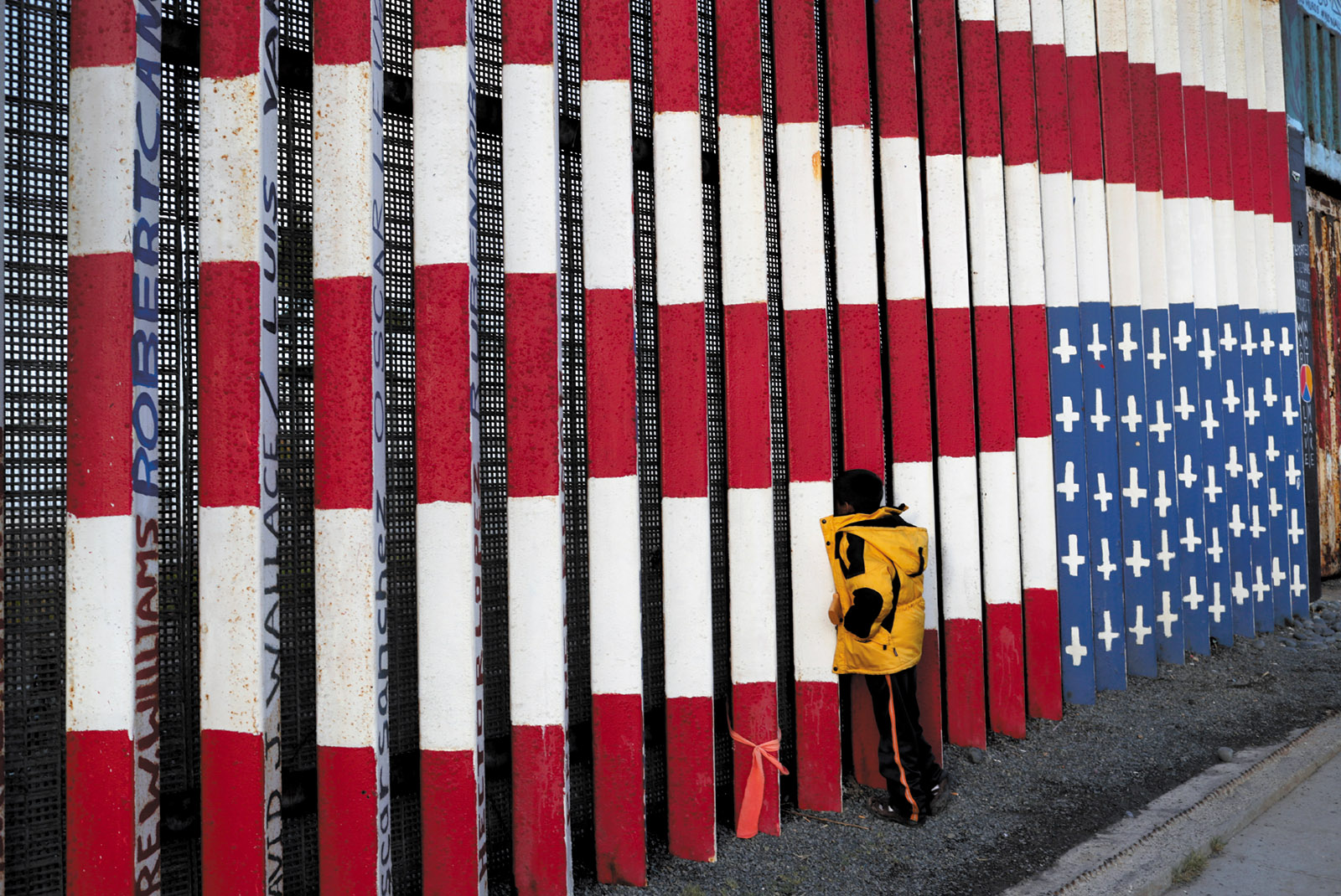 A migrant child looking through the US-Mexico border fence, Tijuana