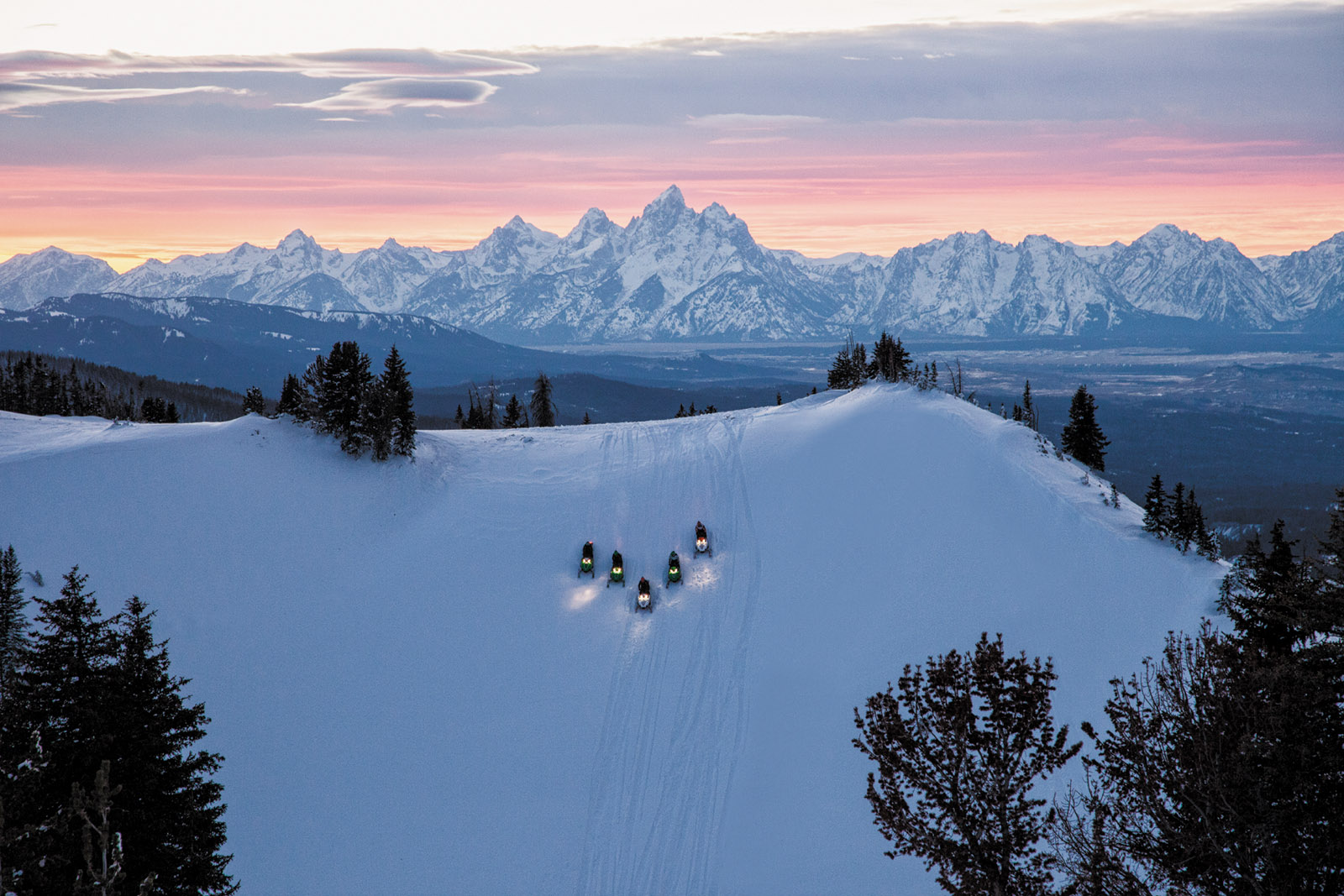 Snowmobilers on Angle Mountain with the Teton Range in the background, Togwotee, Wyoming