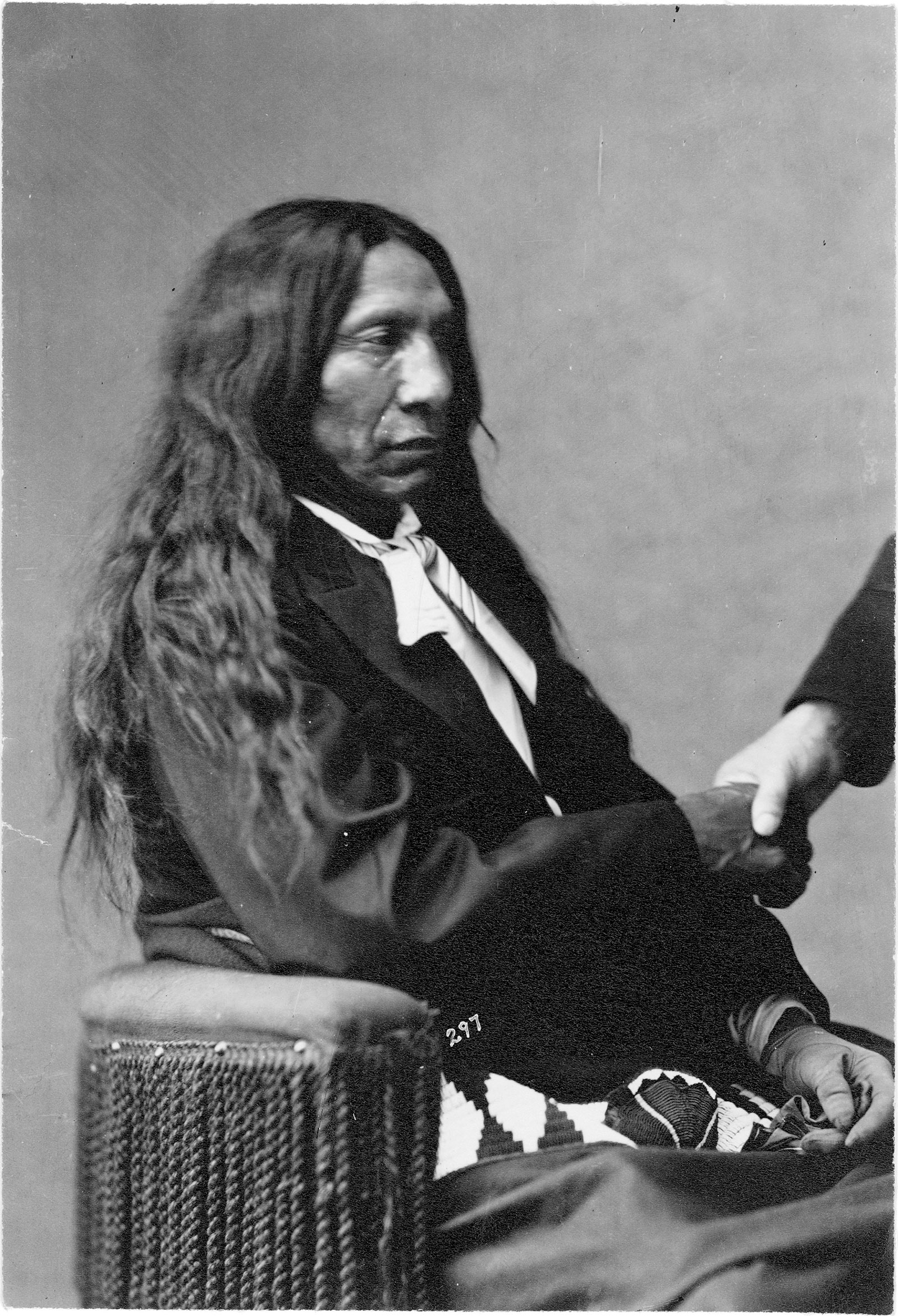 Oglala Lakota Chief Red Cloud in a formal portrait arranged by William Blackmore, whose hand is visible at right