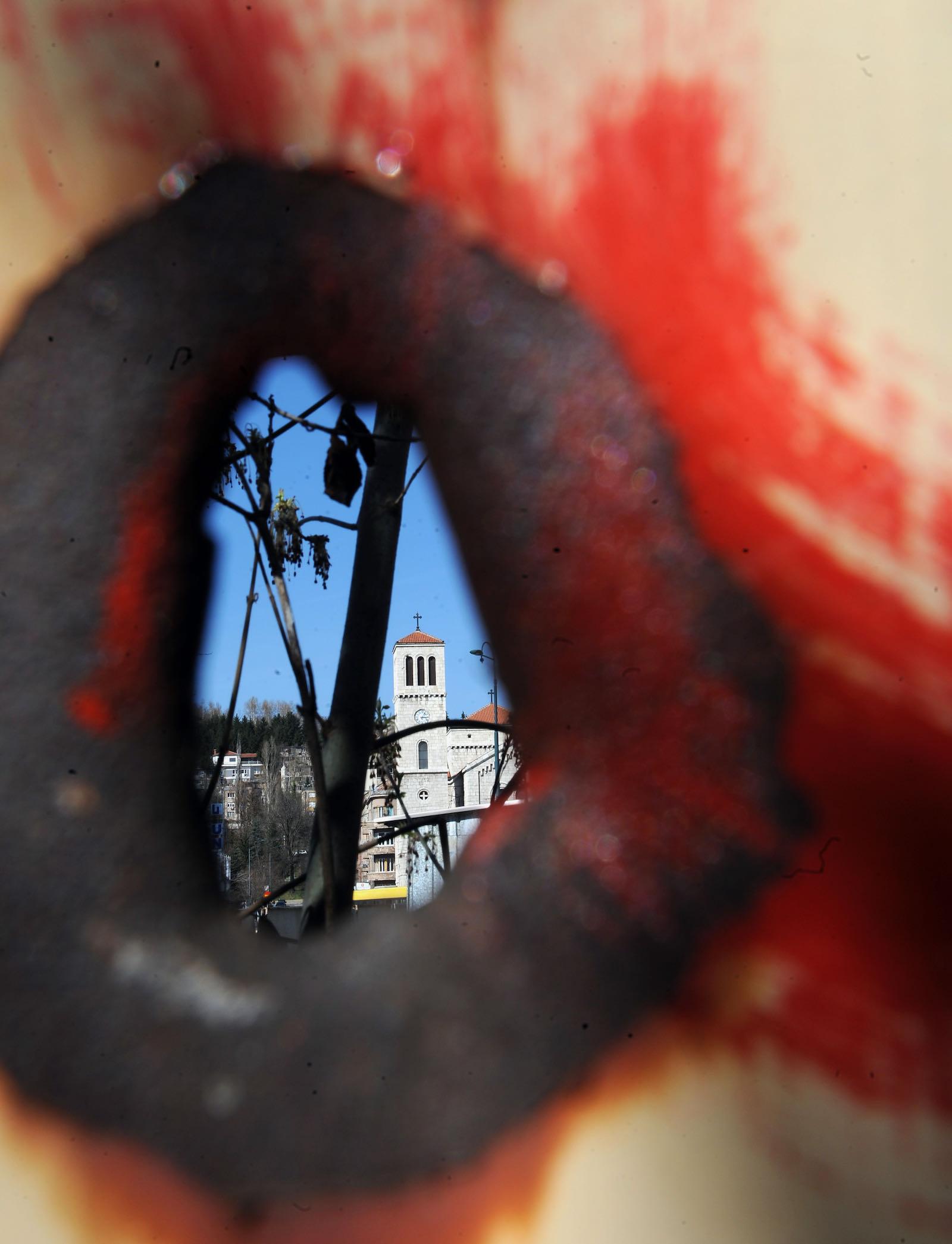 A church on Marijin Dvor Square seen through an old shrapnel hole
