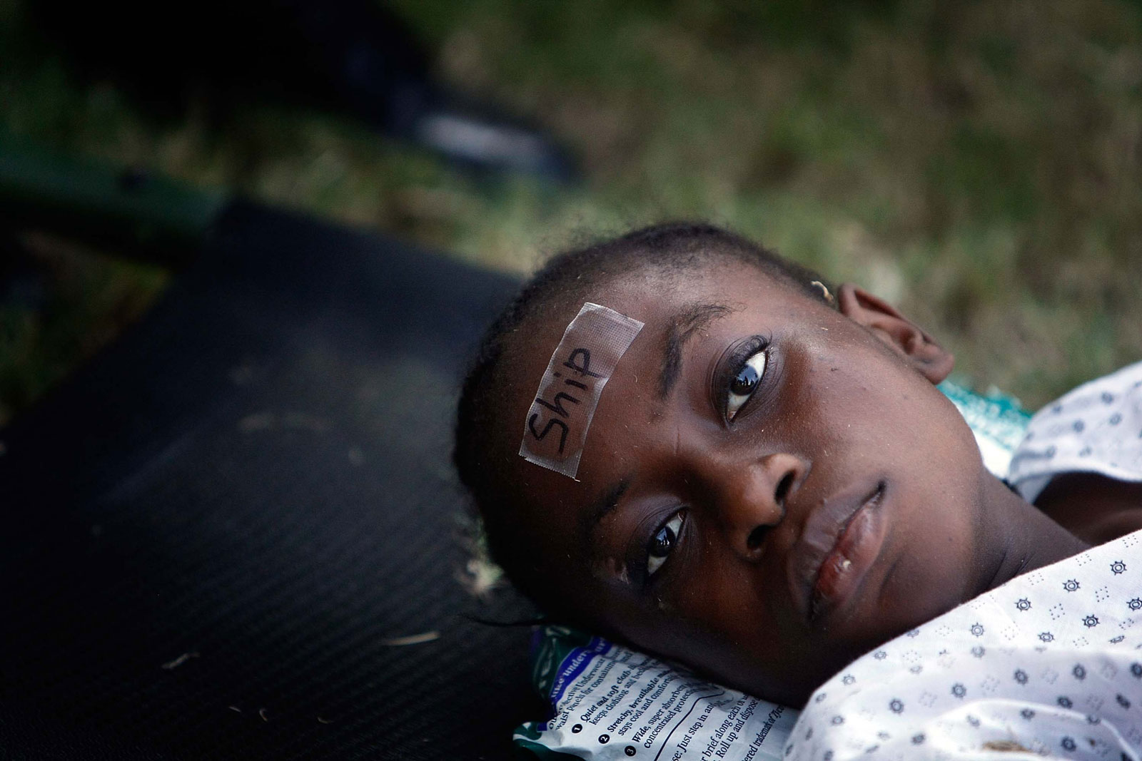 A little girl in Haiti waiting to be medivaced by US Army soldiers after the 2010 earthquake, an image that Christina Sharpe writes about in her book In The Wake