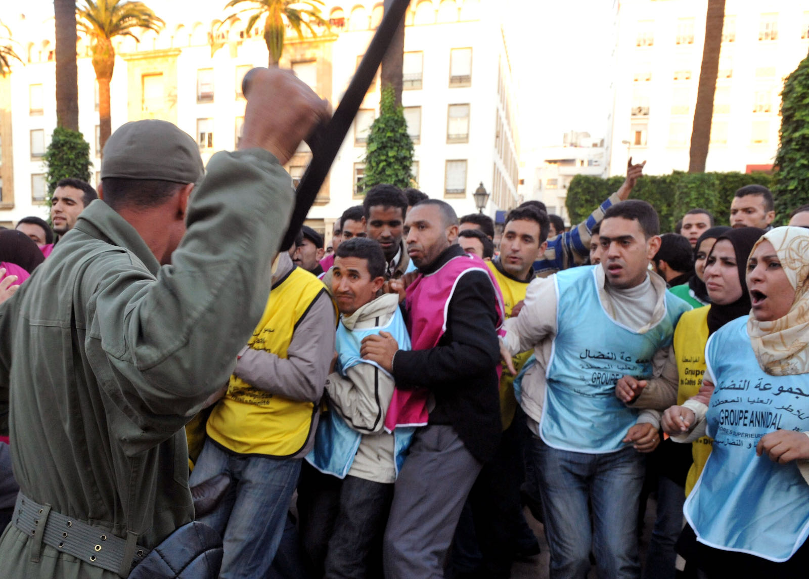 A security guard threatening anti-government protesters