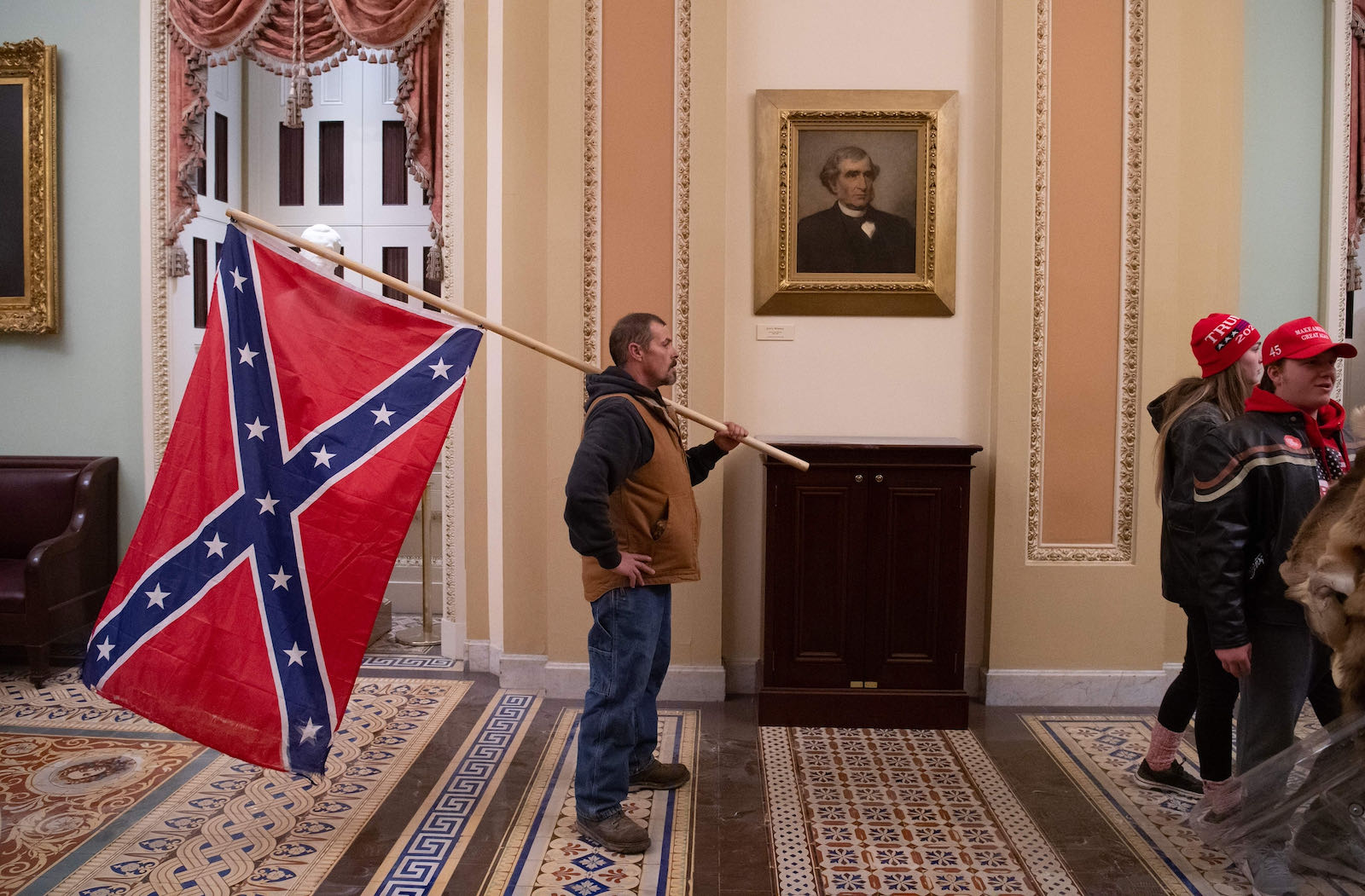 A Trump supporter carrying a Confederate flag, 2021
