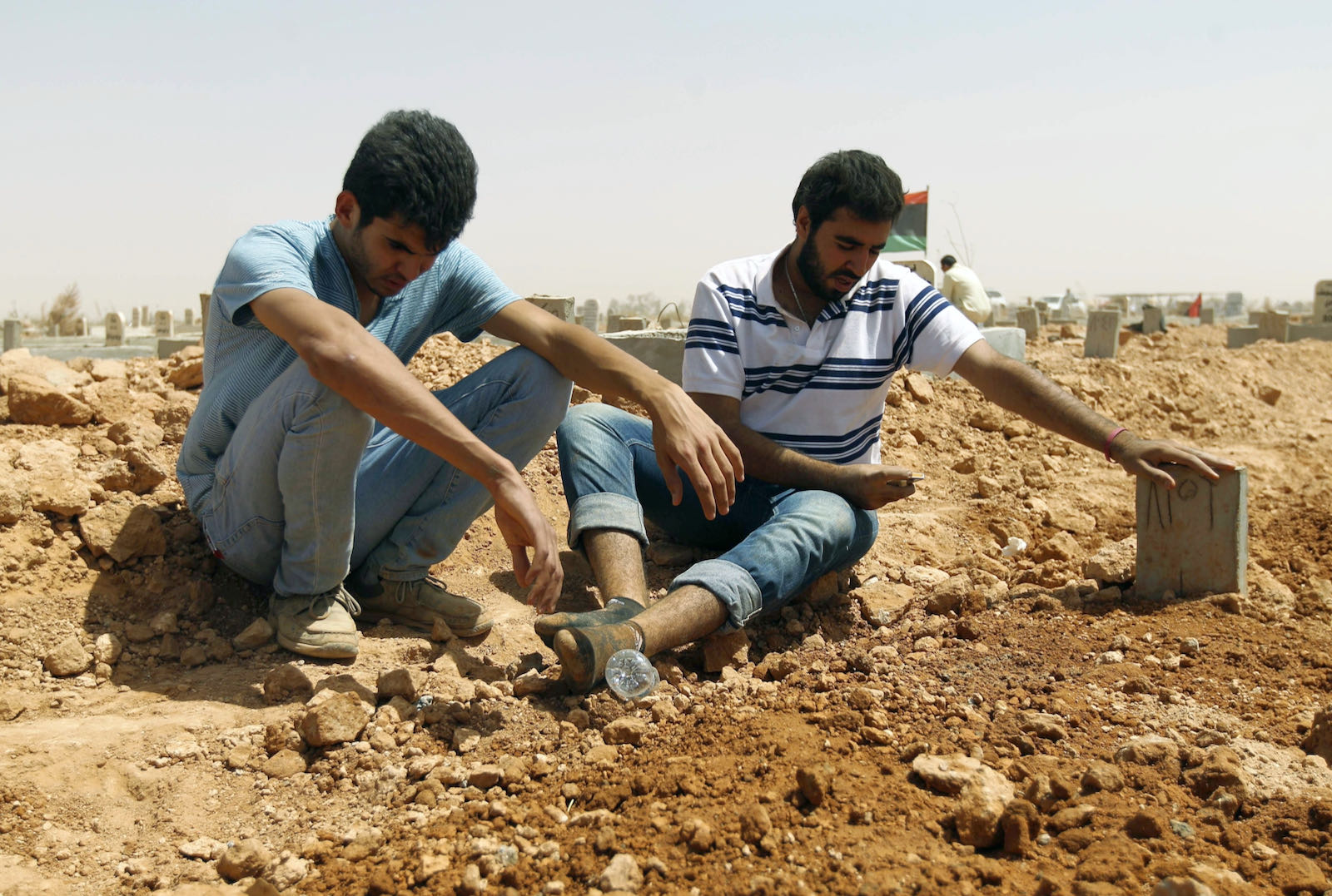 Libyans mourning beside a grave