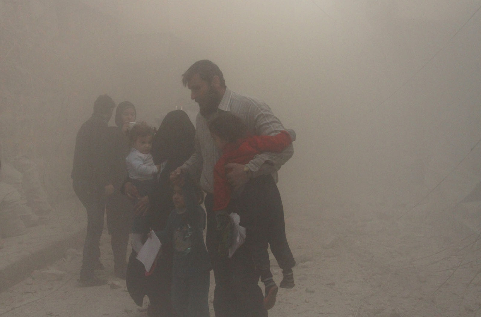 Civilians emerging from destruction caused in a bombing attack