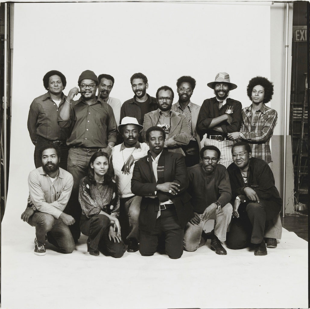 Fourteen members of Kamoinge pose together for a group portrait