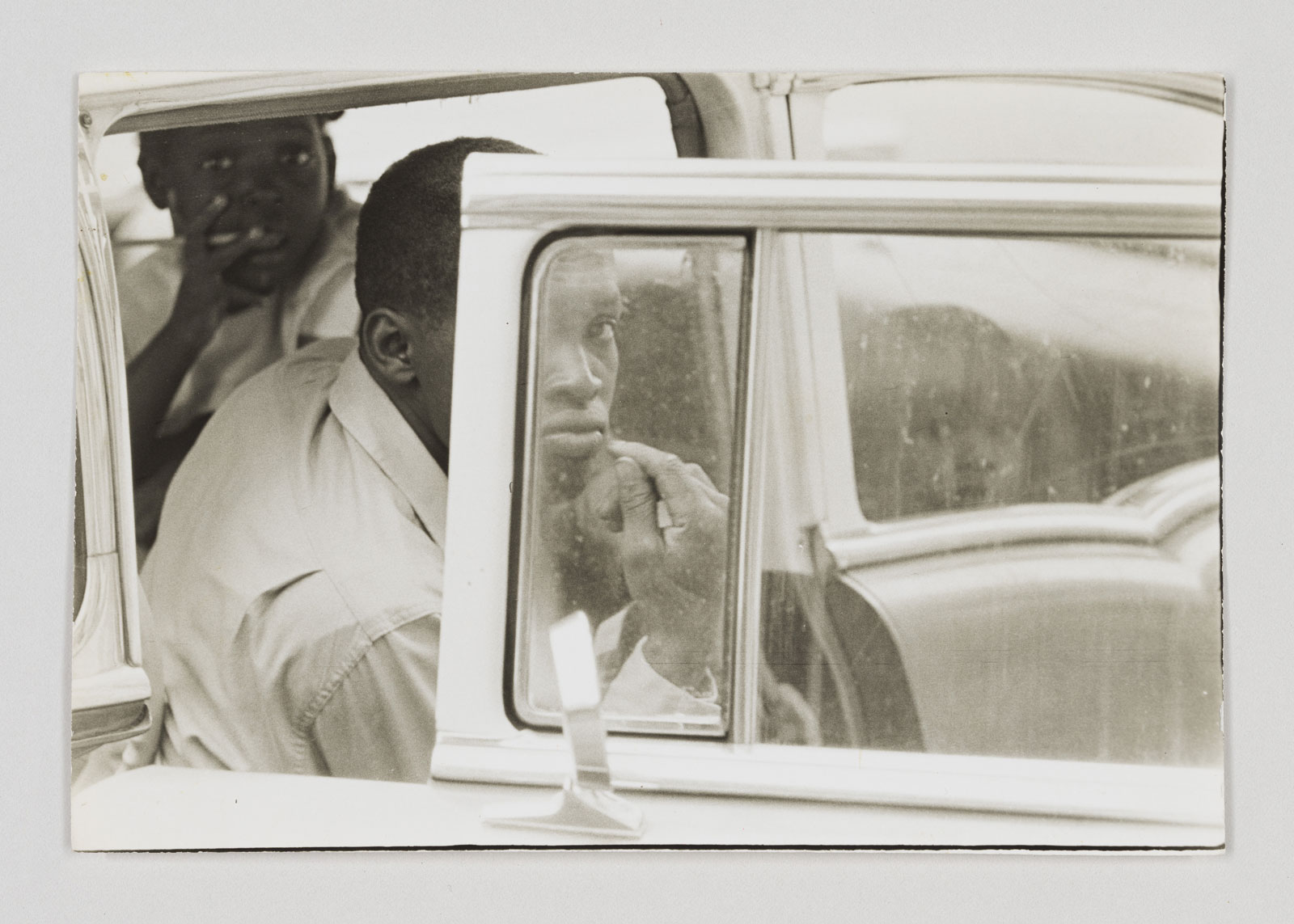 Three boys seen through the window and open door of a parked car