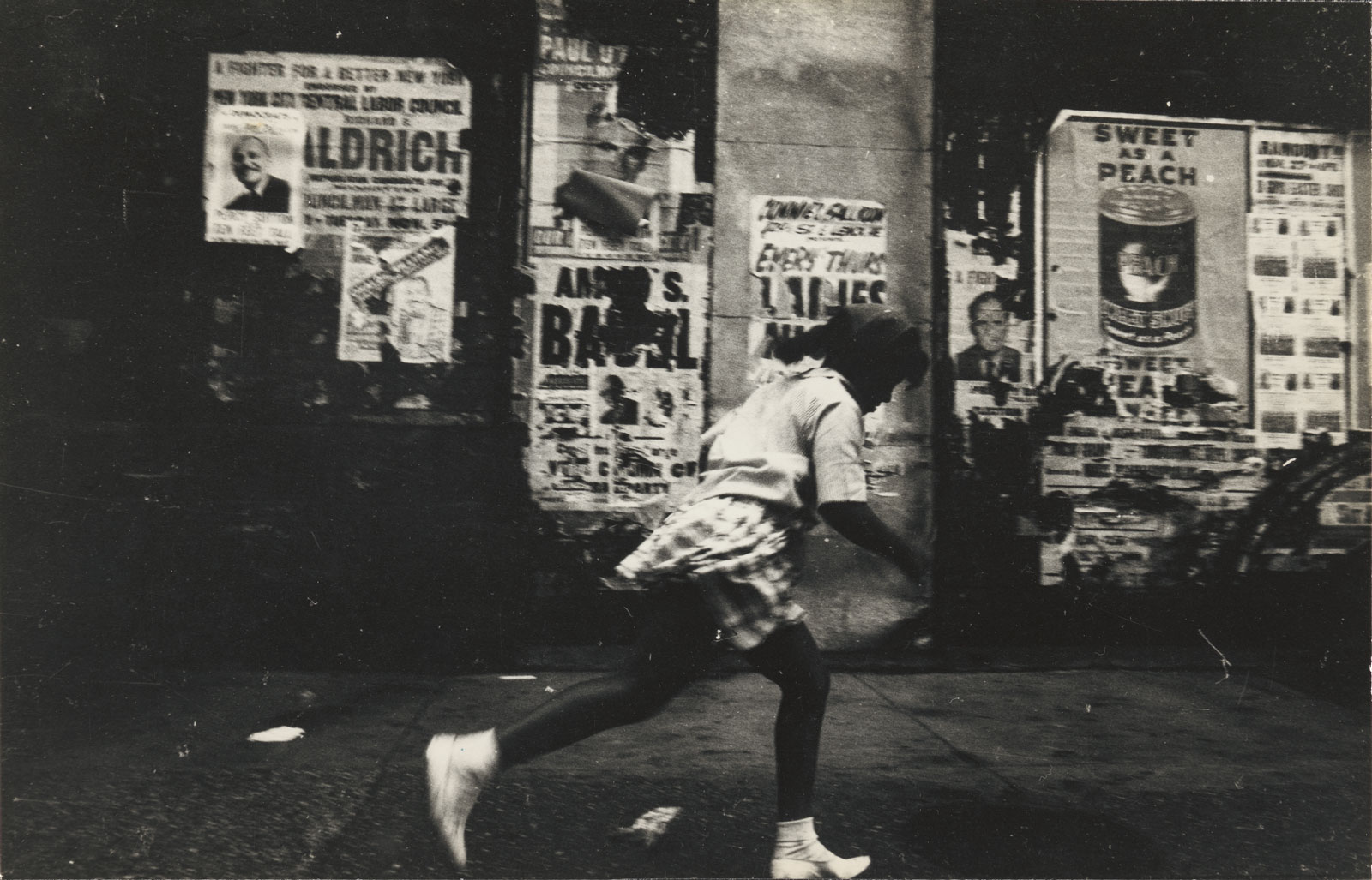 A girl caught in motion running, behind her the peeling posters for Sweet As a Peach and other advertisements