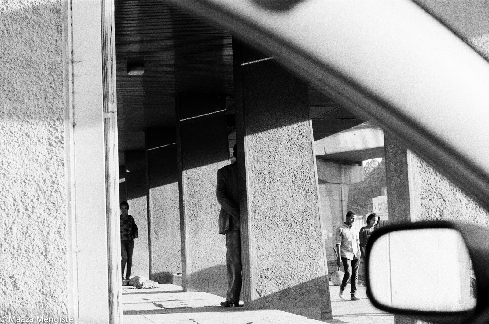 Shadows, columns, and people seen through the window of a car