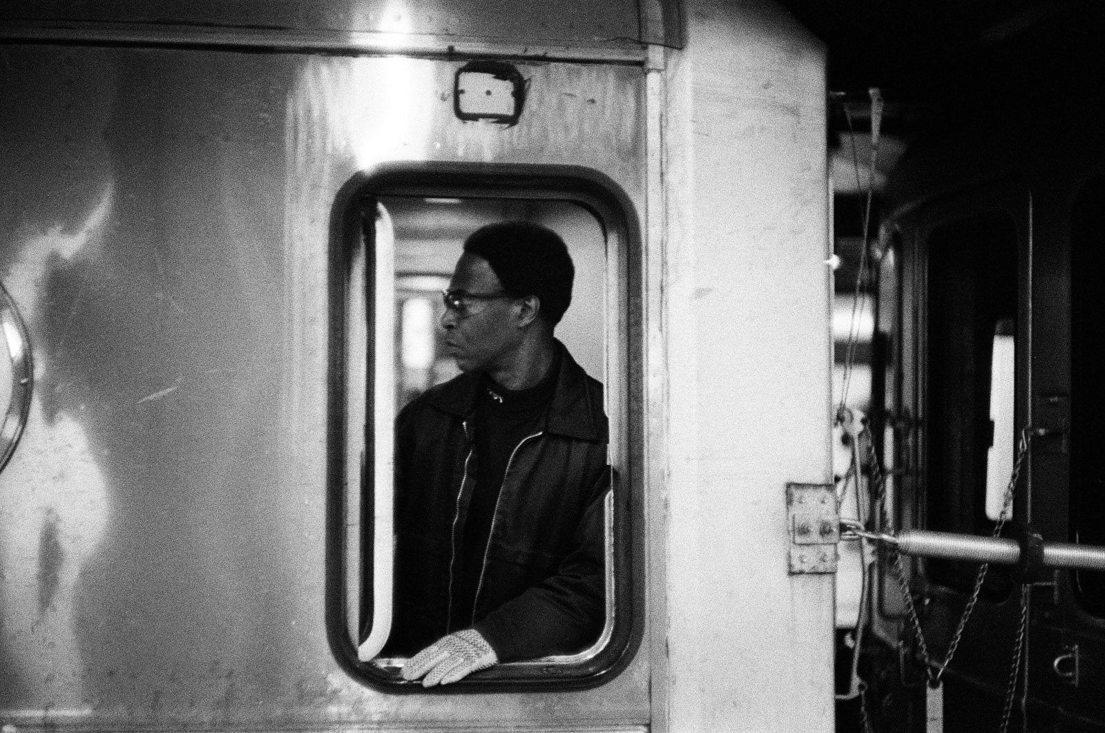 An MTA train conductor in profile, seen through the window of the subway train