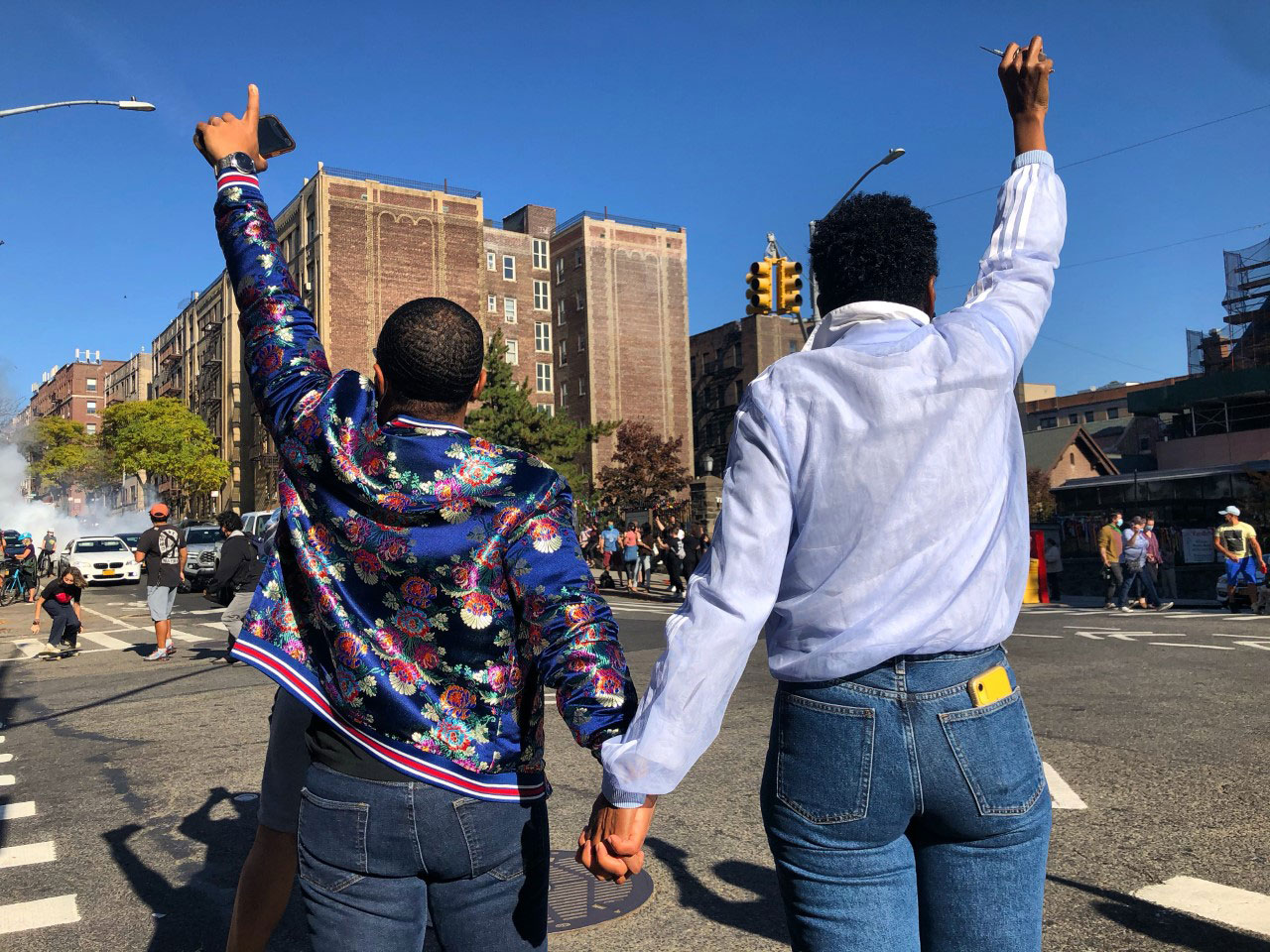 Two women holding hands with their backs facing the camera, cheering toward the street