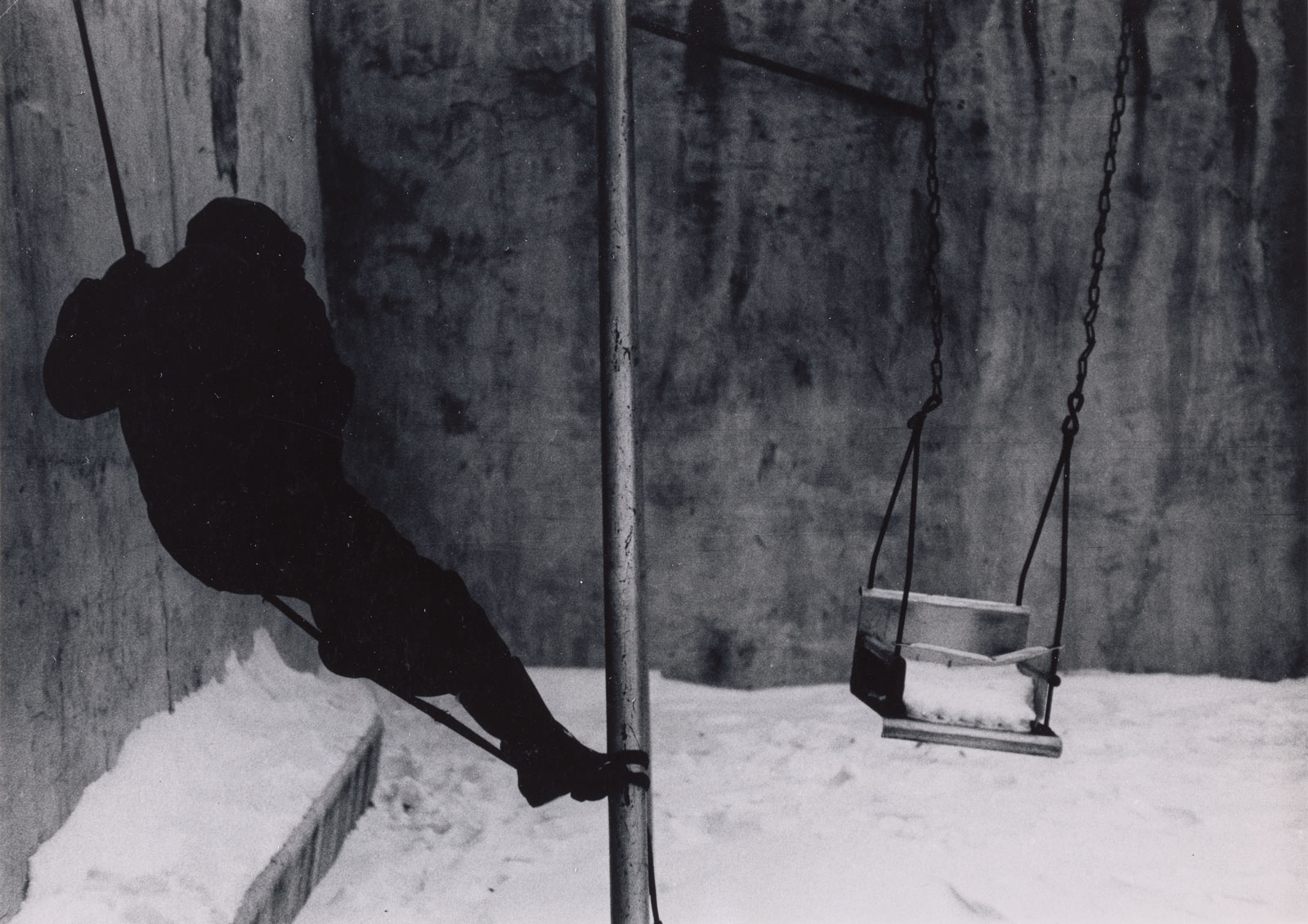 A boy in dark shadows on a swing in the snow