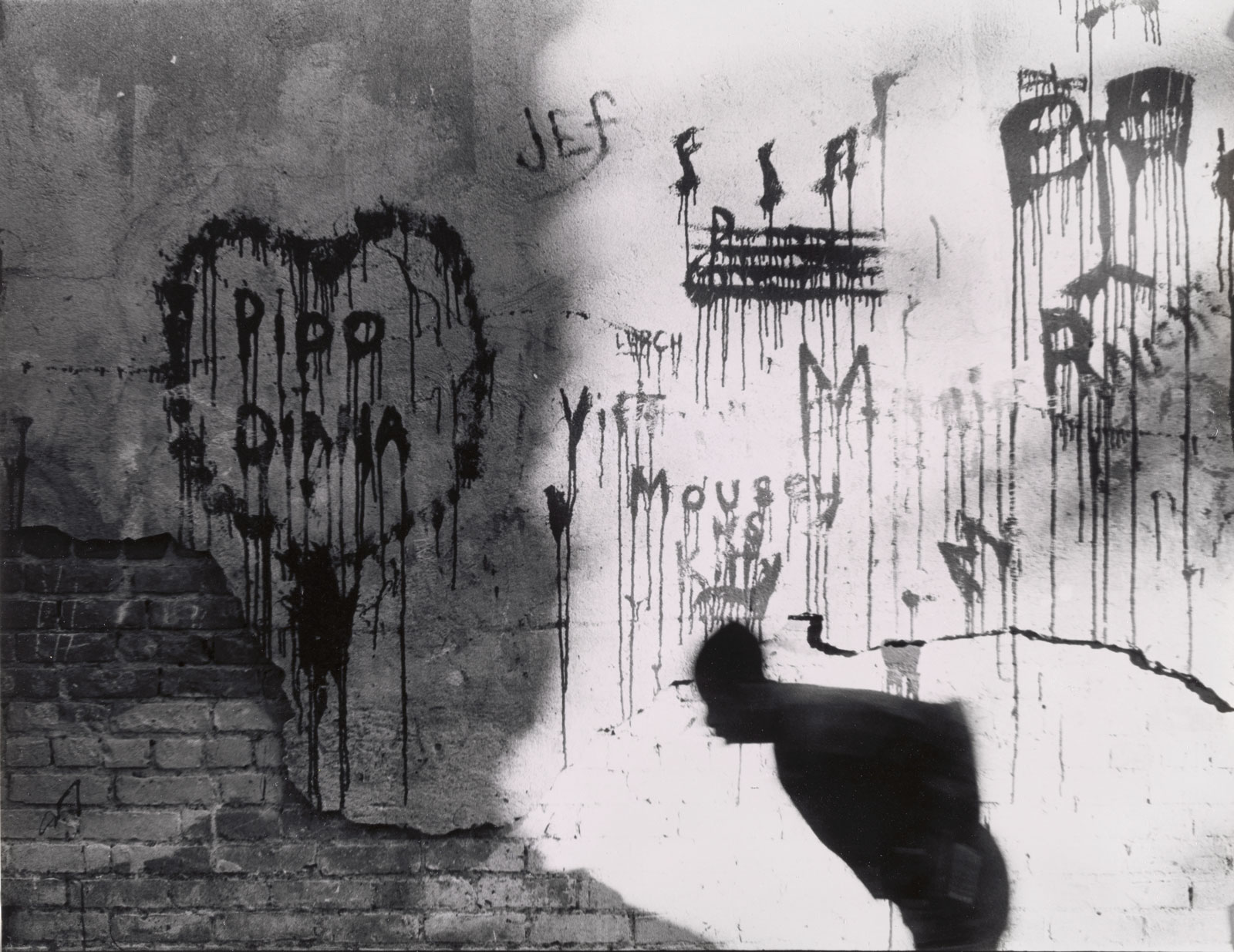 Graffiti bleeding down a wall, as a stooped man passes by