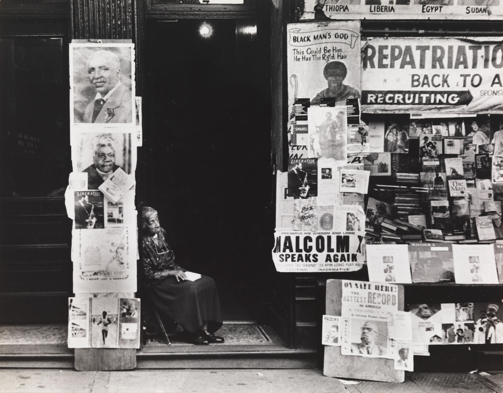 A woman sitting in a doorway nearby a newsstand