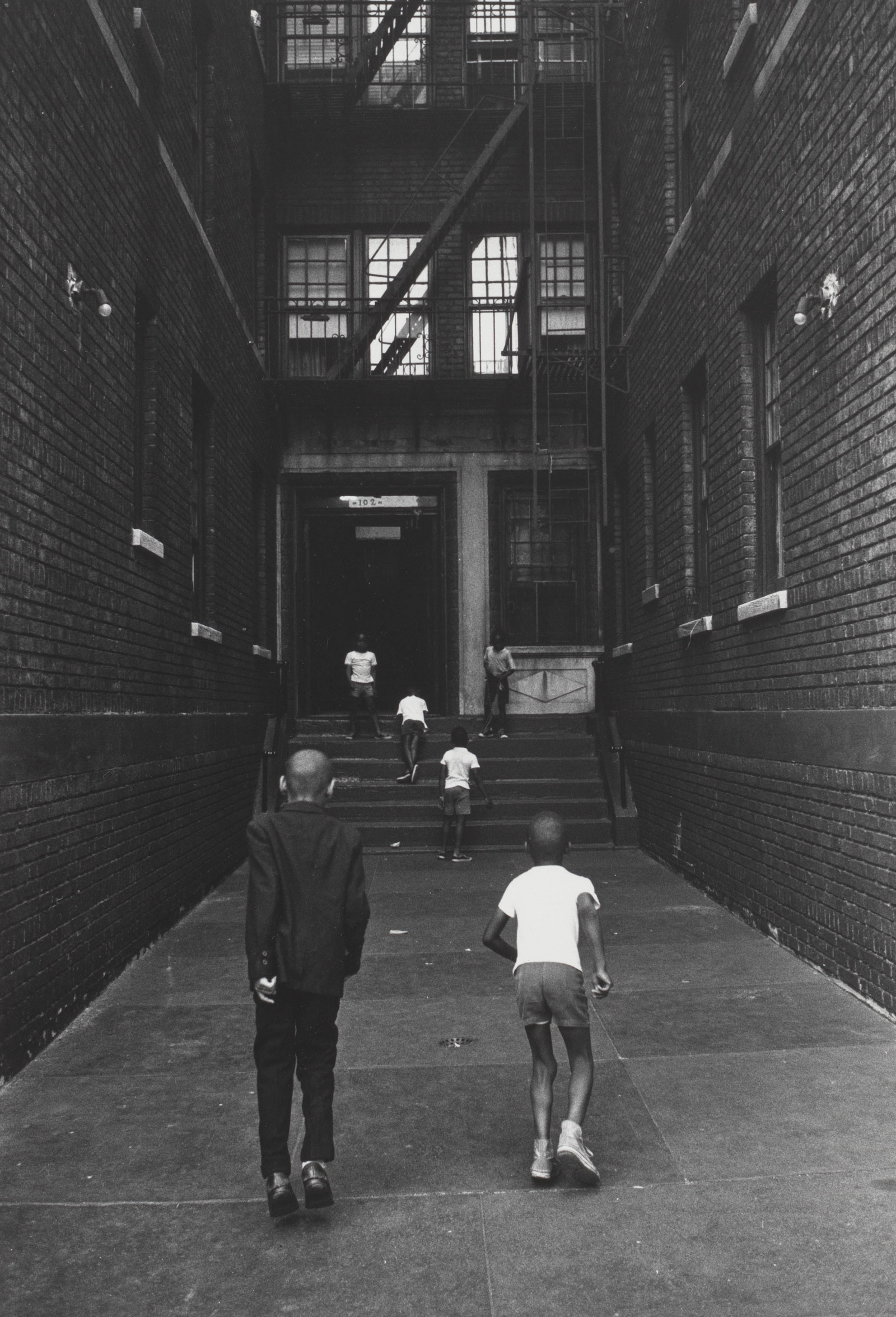 Six children playing in the lot of a New York apartment building