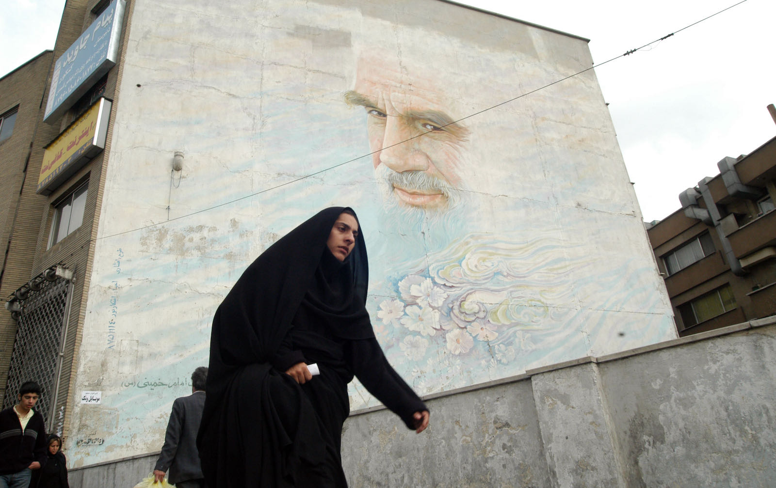 A woman passing by a mural of Ayatollah Khomeini