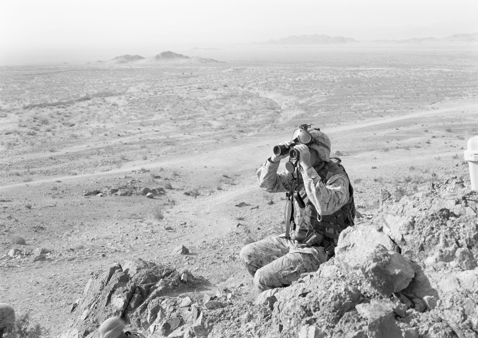 A soldier using binoculars to look out over a hilly area